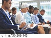 Купить «Business people writing on notepad during seminar», фото № 30209145, снято 21 ноября 2018 г. (c) Wavebreak Media / Фотобанк Лори