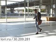 Купить «Businessman using mobile phone while walking in lobby office», фото № 30209281, снято 21 ноября 2018 г. (c) Wavebreak Media / Фотобанк Лори