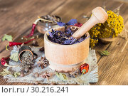 Купить «Fragrant dried healing herbs for therapy and spicy spices. On the table in a mortar purple basil, tansy, pepper, chili and cardamom, in a rustic style», фото № 30216241, снято 16 февраля 2019 г. (c) Светлана Евграфова / Фотобанк Лори