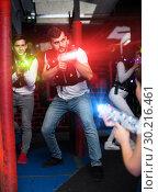 Купить «Emotional guy playing laser tag in colorful beams», фото № 30216461, снято 25 апреля 2018 г. (c) Яков Филимонов / Фотобанк Лори