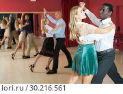 Купить «Positive adult couples dancing tango together in modern studio», фото № 30216561, снято 4 октября 2018 г. (c) Яков Филимонов / Фотобанк Лори