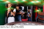Купить «Young guy holding colored laser guns and took aim during laser t», фото № 30216665, снято 23 августа 2018 г. (c) Яков Филимонов / Фотобанк Лори
