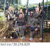 Купить «Friendly group of paintball players in camouflage standing with guns on paintball playing field outdoors», фото № 30216829, снято 11 августа 2018 г. (c) Яков Филимонов / Фотобанк Лори