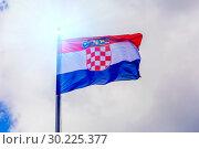 Купить «The national flag of Croatia flutters in the wind against a blue cloudy sky.», фото № 30225377, снято 21 июня 2018 г. (c) Акиньшин Владимир / Фотобанк Лори