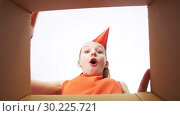 Купить «happy birthday girl in party hat opening gift box», видеоролик № 30225721, снято 27 февраля 2019 г. (c) Syda Productions / Фотобанк Лори