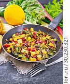 Купить «Мангольд тушеный в сковороде на черной деревянной доске», фото № 30230321, снято 9 сентября 2017 г. (c) Резеда Костылева / Фотобанк Лори