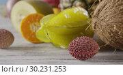 Купить «Close-up dolly slow motion of passion fruit, carambola, litchi on a wooden background. Concept of vegetarian diet eating. Dolly motion, 4K UHD video, 3840, 2160p.», видеоролик № 30231253, снято 4 июля 2018 г. (c) Ярослав Данильченко / Фотобанк Лори