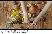 Купить «Womans hands put fresh ripe organic tropical fruits into box with wood shaving on a wooden background. Top view. Fast motion, 4K UHD video, 3840, 2160p.», видеоролик № 30231269, снято 14 февраля 2019 г. (c) Ярослав Данильченко / Фотобанк Лори