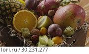 Купить «Droplets water on a fresh juicy exotic fruits in a box on a wooden table. Panoramic motion, 4K UHD video, 3840, 2160p.», видеоролик № 30231277, снято 4 июля 2018 г. (c) Ярослав Данильченко / Фотобанк Лори