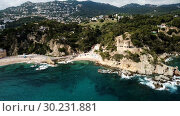 Купить «View from drone of Castell d'en Plaja in Mediterranean coastal town of Lloret de Mar, Catalonia, Spain», видеоролик № 30231881, снято 23 июня 2018 г. (c) Яков Филимонов / Фотобанк Лори