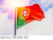 Купить «The national flag of Portugal flutters in the wind against a blue cloudy sky.», фото № 30232121, снято 21 июня 2018 г. (c) Акиньшин Владимир / Фотобанк Лори