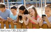 Купить «Children are playing on smartphone in the playground.», видеоролик № 30232281, снято 23 июля 2018 г. (c) Яков Филимонов / Фотобанк Лори