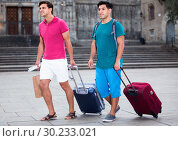 Купить «Men tourists are walking with suitcases in unknown city.», фото № 30233021, снято 19 августа 2017 г. (c) Яков Филимонов / Фотобанк Лори