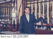 Купить «Handsome adult male owner of hunting shop offering rifle», фото № 30233081, снято 11 декабря 2017 г. (c) Яков Филимонов / Фотобанк Лори