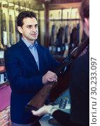 Купить «Man seller in gun shop showing rifle to woman client», фото № 30233097, снято 11 декабря 2017 г. (c) Яков Филимонов / Фотобанк Лори
