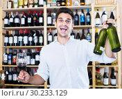 Купить «Seller holding bottle of wine», фото № 30233129, снято 20 мая 2019 г. (c) Яков Филимонов / Фотобанк Лори