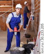 Купить «Workers doing repair work», фото № 30233205, снято 12 февраля 2019 г. (c) Яков Филимонов / Фотобанк Лори