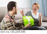 Купить «Son gives gift to mother», фото № 30234545, снято 18 марта 2019 г. (c) Яков Филимонов / Фотобанк Лори