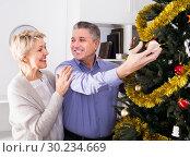 Купить «Mature vigorous couple decorate fir-tree for holidays of Christmas and New Year», фото № 30234669, снято 19 марта 2019 г. (c) Яков Филимонов / Фотобанк Лори