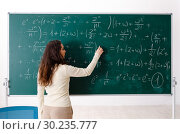 Young female math teacher in front of chalkboard. Стоковое фото, фотограф Elnur / Фотобанк Лори