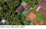 Купить «Houses with colorful shingle roofs and pool with swimming woman between palm trees», видеоролик № 30237397, снято 23 января 2019 г. (c) Andriy Bezuglov / Фотобанк Лори
