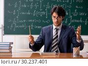 Купить «Young male math teacher in classroom», фото № 30237401, снято 11 октября 2018 г. (c) Elnur / Фотобанк Лори