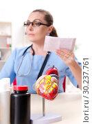 Купить «Female doctor cardiologist working in the clinic», фото № 30237761, снято 22 ноября 2018 г. (c) Elnur / Фотобанк Лори