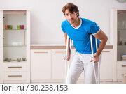 Купить «Leg injured young man with crutches at home», фото № 30238153, снято 19 сентября 2018 г. (c) Elnur / Фотобанк Лори