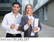 Купить «Portrait of couple who are standing with folder and coffee», фото № 30242297, снято 20 августа 2017 г. (c) Яков Филимонов / Фотобанк Лори