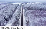 Купить «Winter road with ice on the asphalt, trees under snow during the winter frost», видеоролик № 30242721, снято 5 марта 2019 г. (c) Mikhail Starodubov / Фотобанк Лори