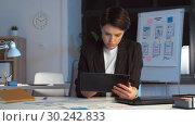 Купить «ui designer with tablet pc working at night office», видеоролик № 30242833, снято 28 февраля 2019 г. (c) Syda Productions / Фотобанк Лори