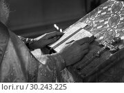 Black and white Priest praying in the church holding holly bible and cross with candles. Стоковое фото, фотограф Валерий Моисеев / Фотобанк Лори