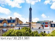 Купить «Eifel tower over the buildings in Paris downtown», фото № 30251981, снято 6 августа 2016 г. (c) Сергей Новиков / Фотобанк Лори