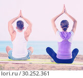 Купить «Woman and man sitting cross-legged do yoga poses on beach», фото № 30252361, снято 24 марта 2019 г. (c) Яков Филимонов / Фотобанк Лори
