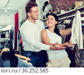 Купить «Young customers selecting jacket», фото № 30252585, снято 24 октября 2016 г. (c) Яков Филимонов / Фотобанк Лори