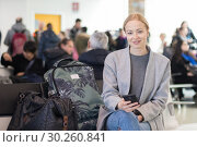 Купить «Cheerful female traveler smiling, looking at camera while reading on her cell phone while waiting to board a plane at departure gates at airport terminal.», фото № 30260841, снято 10 января 2019 г. (c) Matej Kastelic / Фотобанк Лори