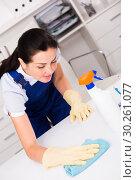 Купить «Young and smiling woman in gloves cleaning table», фото № 30261077, снято 2 июня 2017 г. (c) Яков Филимонов / Фотобанк Лори
