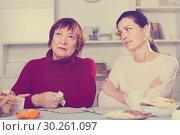 Купить «Unhappy adult female quarrel with daughter at table», фото № 30261097, снято 23 ноября 2017 г. (c) Яков Филимонов / Фотобанк Лори