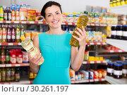 Купить «Woman choosing different oil in bottle», фото № 30261197, снято 6 июня 2017 г. (c) Яков Филимонов / Фотобанк Лори