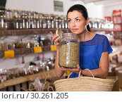 Купить «adult female take a smell natural dried herbs sold by weight in eco shop», фото № 30261205, снято 13 июня 2017 г. (c) Яков Филимонов / Фотобанк Лори