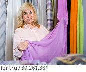 Купить «Portrait of smiling mature woman choosing draperies», фото № 30261381, снято 17 января 2018 г. (c) Яков Филимонов / Фотобанк Лори
