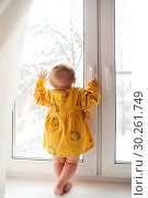 Купить «little girl of 9 months standing on window sill .», фото № 30261749, снято 26 марта 2019 г. (c) Дарья Филимонова / Фотобанк Лори