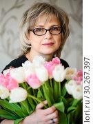 Купить «Симпатичная женщина среднего возраста с большим букетом тюльпанов», эксклюзивное фото № 30267397, снято 18 февраля 2019 г. (c) Игорь Низов / Фотобанк Лори