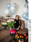 Купить «Симпатичная женщина средних лет сидит на диване и смотрит вверх. Много цветов и воздушные шары», эксклюзивное фото № 30267485, снято 18 февраля 2019 г. (c) Игорь Низов / Фотобанк Лори