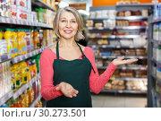 Купить «mature saleswoman inviting to grocery store», фото № 30273501, снято 8 февраля 2019 г. (c) Яков Филимонов / Фотобанк Лори