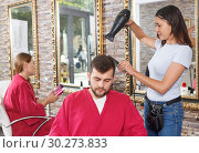 Купить «Young woman hairstylist drying hair with blow dryer of guy», фото № 30273833, снято 25 апреля 2018 г. (c) Яков Филимонов / Фотобанк Лори