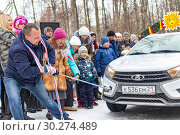 Купить «A man participates in the competition for the holiday Maslenitsa and drags a lightweight LADA car on a rope. City of Cheboksary, Russia, 03/10/2019.», фото № 30274489, снято 10 марта 2019 г. (c) Александр Якимов / Фотобанк Лори