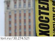 """Купить «Объявление на столбе с рекламой хостела на фоне фасада здания гостиницы Hilton Moscow Leningradskaya 5* (""""Ленинградская"""") на Комсомольской площади в центре города Москвы, Россия», фото № 30274521, снято 10 марта 2019 г. (c) Николай Винокуров / Фотобанк Лори"""