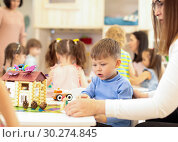 Купить «Kindergarten child boy building toy house in playroom at preschool, education concept.», фото № 30274845, снято 7 июня 2020 г. (c) Оксана Кузьмина / Фотобанк Лори