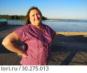 Middle-aged woman standing on river embankment relaxing and smiling. Стоковое фото, фотограф Дмитрий Морозов / Фотобанк Лори